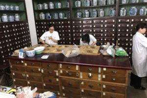 中国の薬局で漢方薬を分けるようす